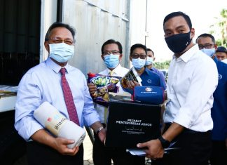 Johor Menteri Besar, Datuk Ir. Hasni Mohammad showing the items for the food box with State Youth and Sports and Tourism Committee chairman Datuk Onn Hafiz Ghazi holding the packaging of the food basket